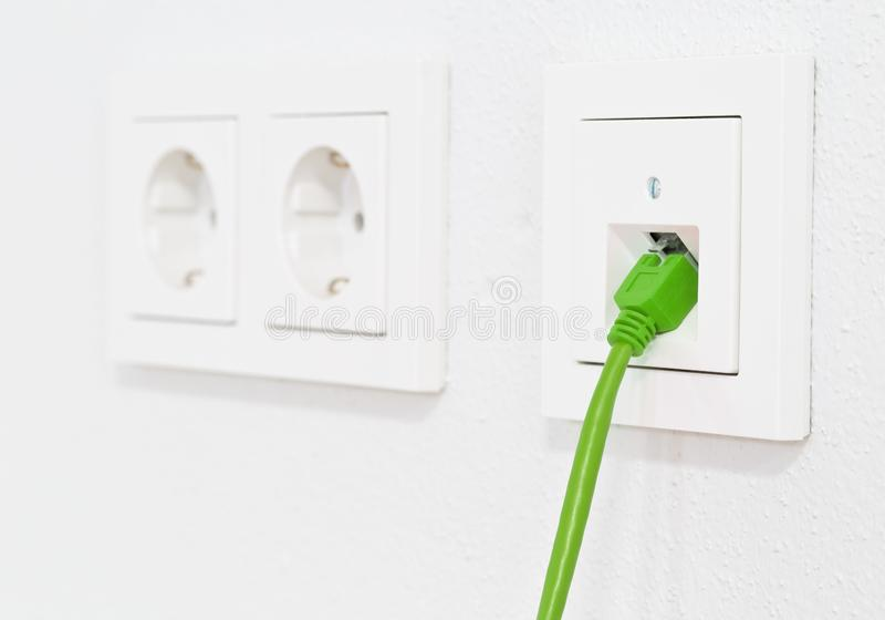 Green network cable in wall outlet for office or private home lan ethernet connection with power outlets flat view on white royalty free stock images