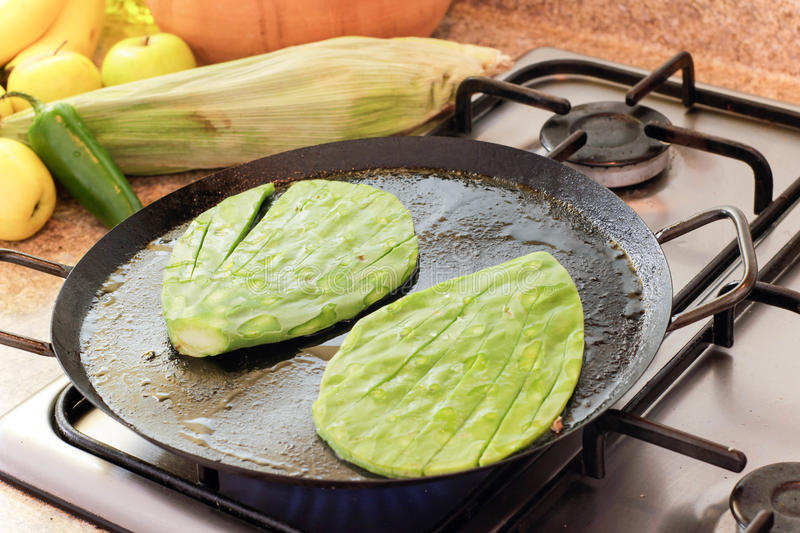 Green nopal cactus on hot pan. Photograph of some nopals on a hot pan on a stove royalty free stock image