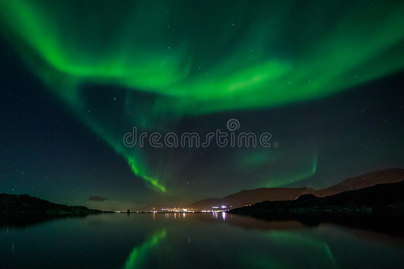 Green Northern lights reflecting in the lake with mountains and city in the background, Nuuk, Greenland. Anomaly, arctic, aurora, backgrounds, beauty, borealis royalty free stock photos