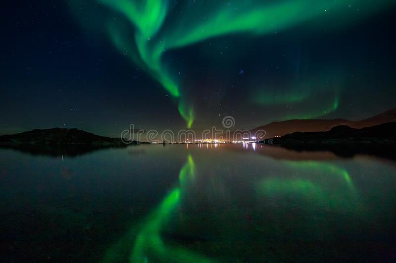 Green Northern lights reflecting in the lake with mountains and city in the background, Nuuk, Greenland. Anomaly, arctic, aurora, backgrounds, beauty, borealis stock photo