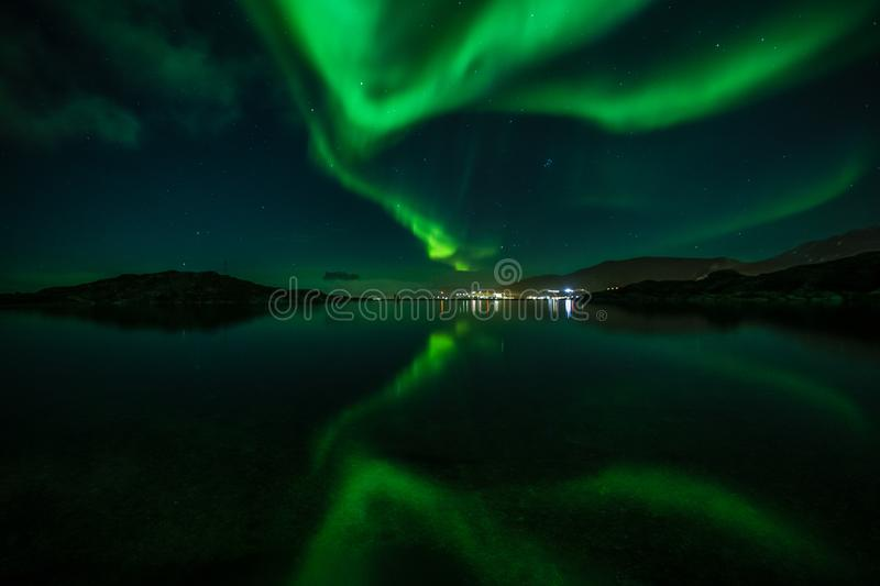 Green Northern lights reflecting in the lake with mountains and city in the background, Nuuk, Greenland. Arctic, astronomy, aurora, backgrounds, beauty stock images