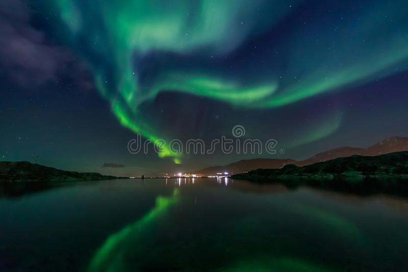 Green Northern lights reflecting in the lake with mountains and. City in the background, Nuuk, Greenland stock photography