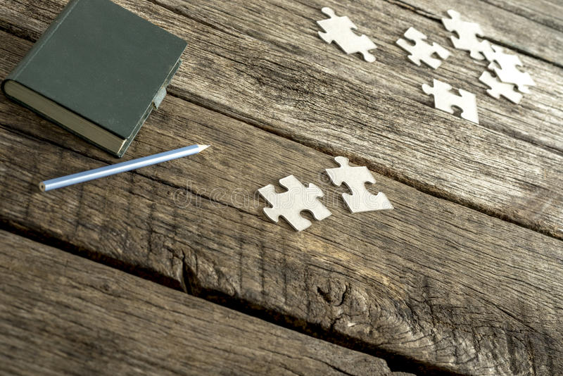 Green note pad, pencil and scattered puzzle pieces lying on a te stock photography