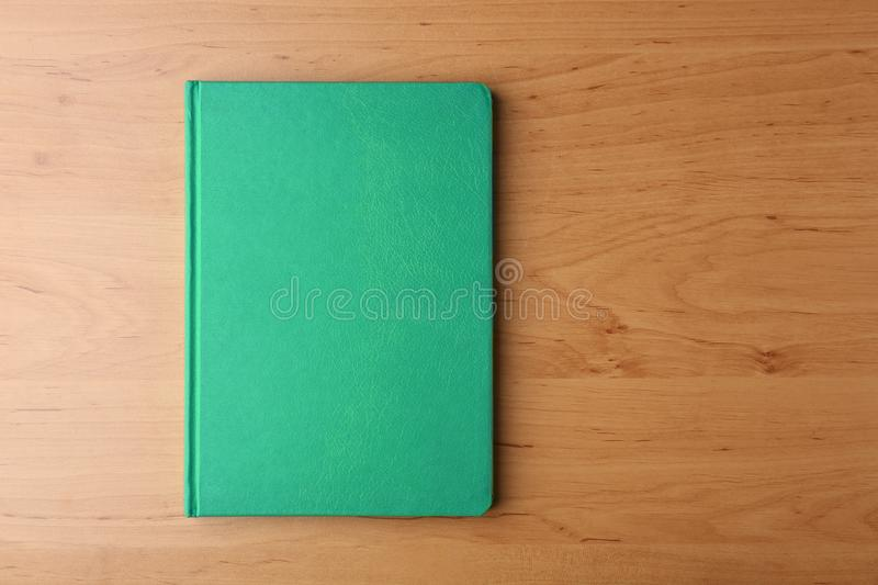 Green notebook for branding. On wooden background stock image