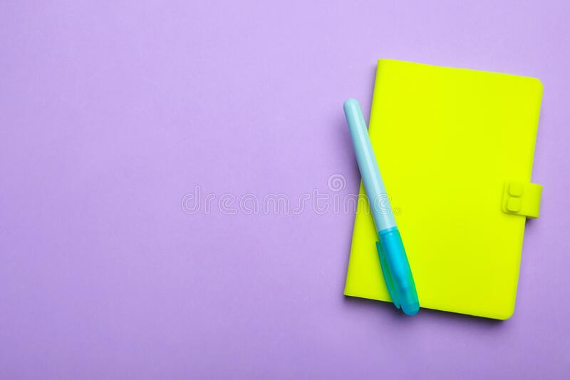 Green notebook and marker on lilac, top view. Space for text stock photo