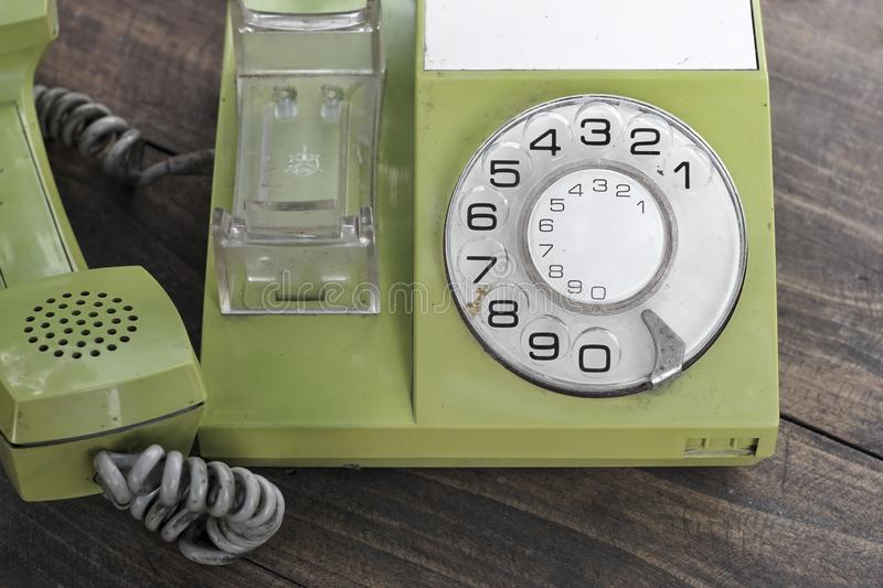 Green old-fashioned telephone on wooden background. From above royalty free stock image