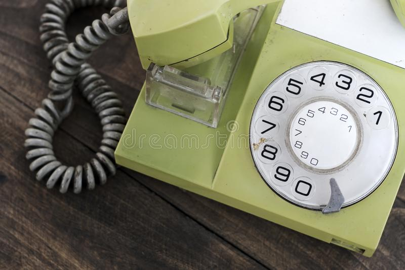 Green old-fashioned telephone on wooden background. From above stock image