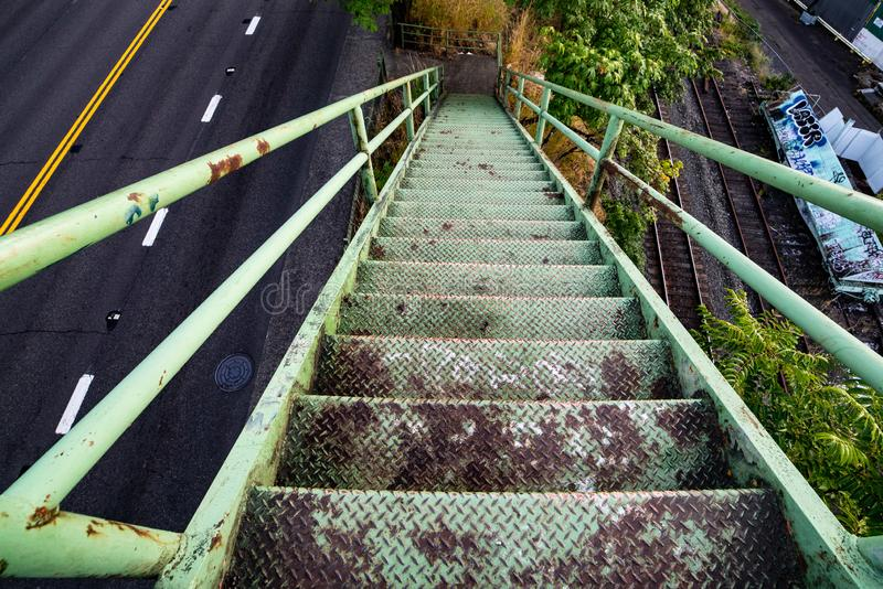 Green old rusted stairs going down. Onto the sidewalk next to the highway. View form above royalty free stock photography