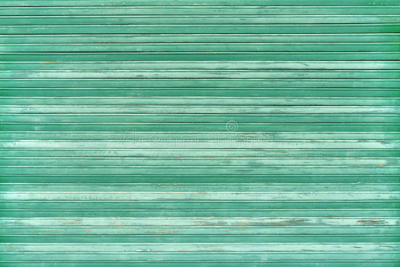 Green old weathered blind made of wood. Green old weathered closed blind made of wood in close-up royalty free stock photo