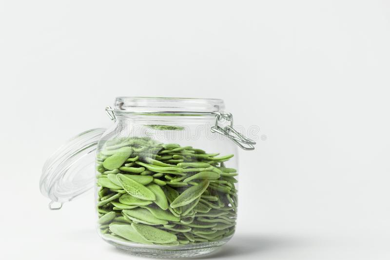 Green olive leaves pasta in glass crystal storage jar with open lid on white table wall background. Italian cuisine specialty. Kitchen organization solutions stock image