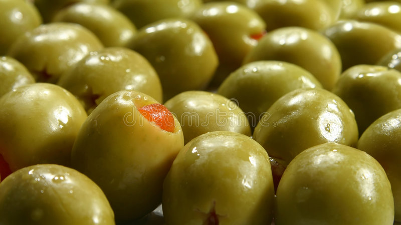 Green olives. Stuffed with red pepper stock photos