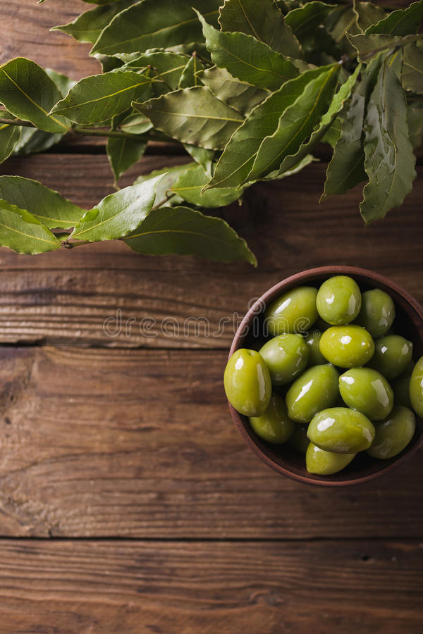 Green olives in a ceramic bowl on a wooden background. Background of olives. Background with green olives. Olives. Copyspace. Green olives and branch of bay royalty free stock photos
