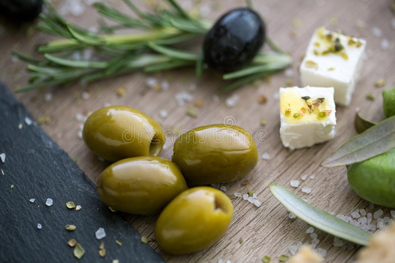 Green olives and feta cheese with olive oil royalty free stock photo