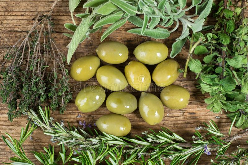 Green olives with several herbs around on wooden table. royalty free stock photography