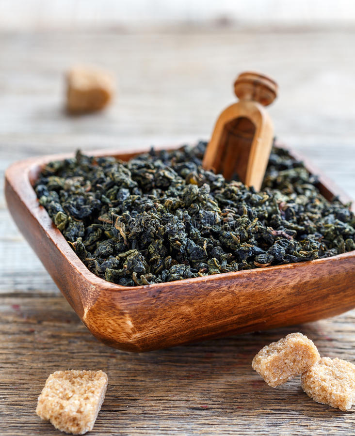 Green oolong tea in a wooden bowl. royalty free stock images