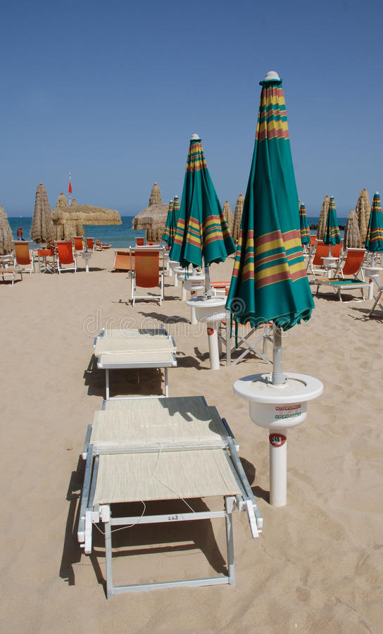 Green and Orange Beach Umbrellas. And deckchairs on a beach on a sunny summers day stock images