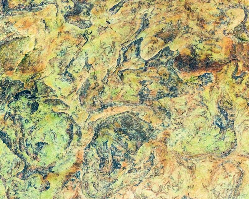 Green, orange, blue and yellow sedimentary rocks - colourful rock layers formed through cementation and deposition - abstract royalty free stock image