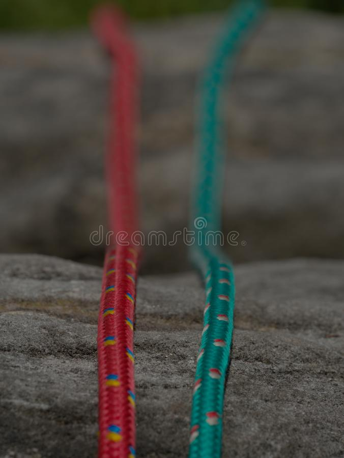 Green and orange nylon rope on natural rock background stock images
