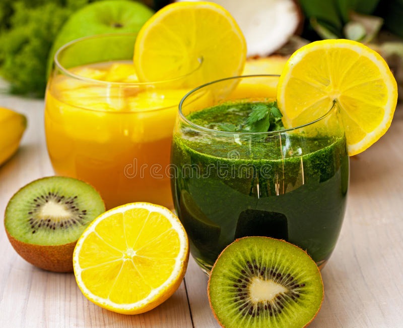 Green and orange smoothies. Refreshing green and orange smoothies with fruit stock photo
