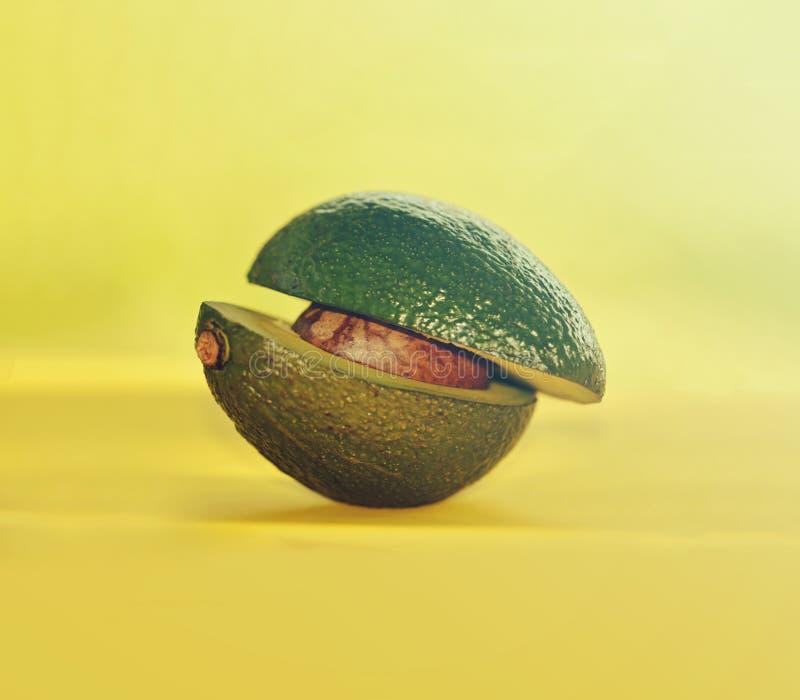 Green organic avocado. Green organic avocado on yellow background royalty free stock image
