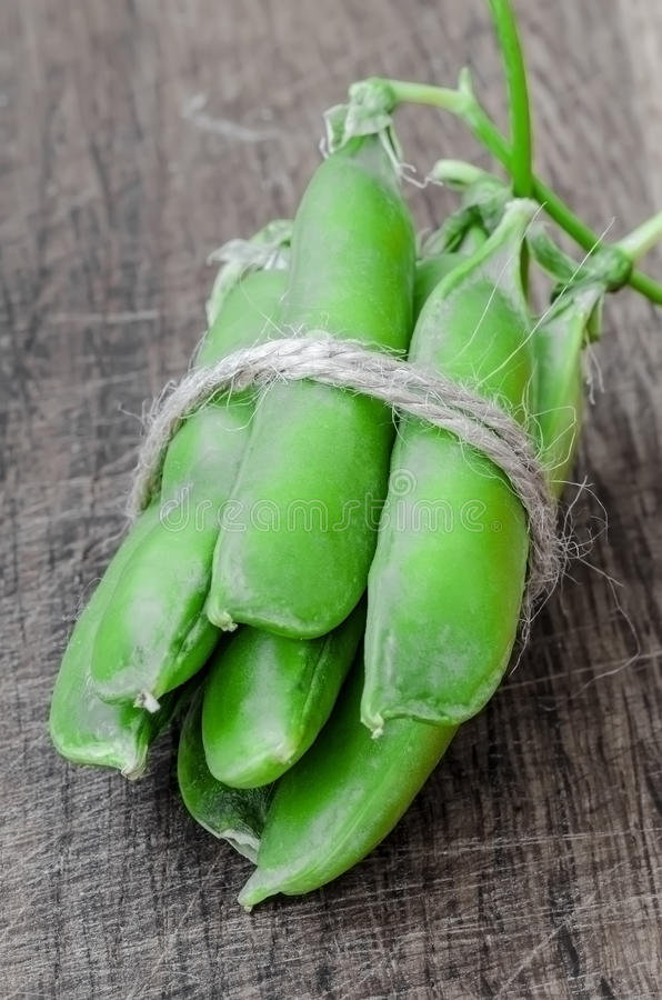 Green organic peas on wooden background. Shallow focus stock photo