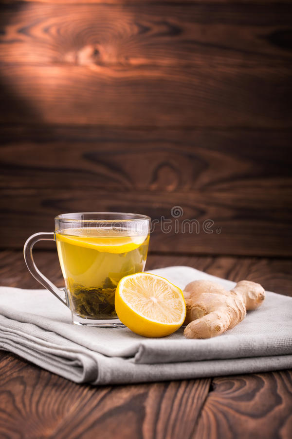 Green organic tea. A tea cup on a dark wooden background. A glass cup filled with liquid, natural green tea leaves, and lemon. stock photo