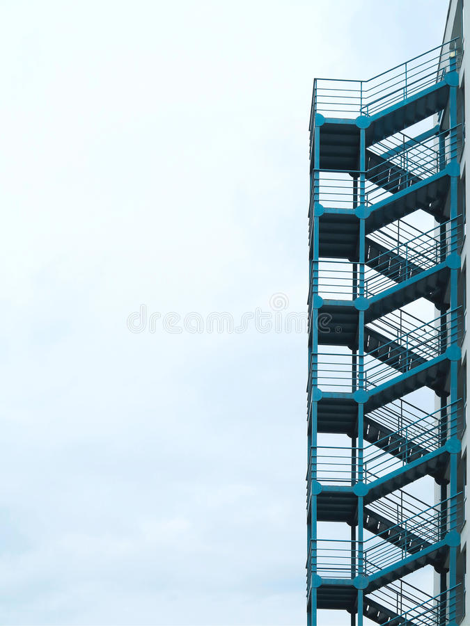 Green outside fire escape stairs ladder over cloudy sky stock images