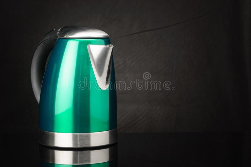 Green stainless steel kettle on black mirror background with copy space stock photo
