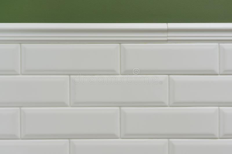 Green painted wall, part of the wall is covered tiles small white glossy brick, ceramic decorative molding tiles. Fragment of the stock image
