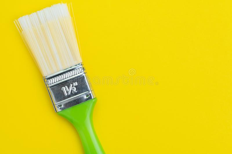 Green painting brush on solid yellow background with copy space using as art, color palette or design concept.  royalty free stock photography