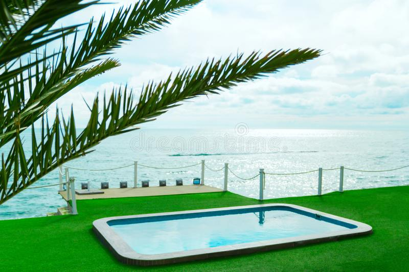 Palm leaf and turquoise water of the swimming pool by the sea ,summer vacation and luxury living concept. Green palm leaf and turquoise water of the  swimming stock images