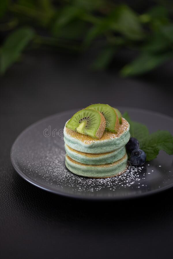 Green Pancakes on a black table with green kiwi royalty free stock photography
