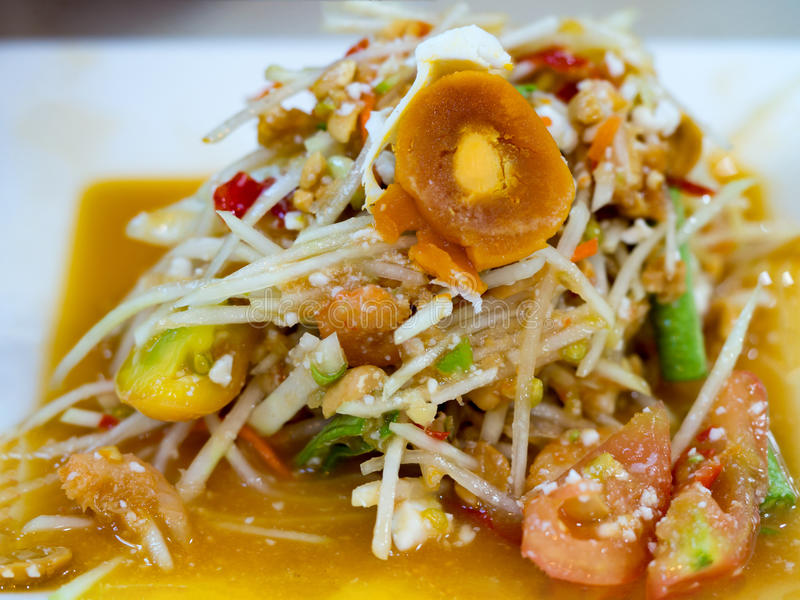 Green papaya salad or Som tum with preserved egg. Popular Thai local food. Spicy salad from shredded unripe papaya, sliced tomato royalty free stock image