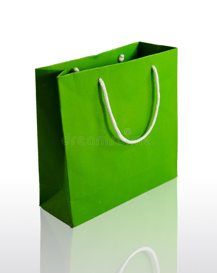 Green paper bag. On reflect floor and white background royalty free stock image