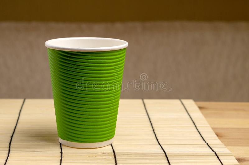 Green paper cup on bamboo stand. Ecological dishes.  royalty free stock images