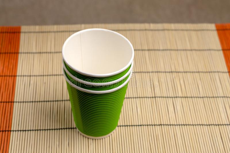 Green paper cups in green on a bamboo stand, top view.  stock image