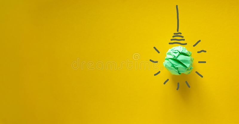 Green paper light bulb. Corporate social responsibility, responsible business, eco friendly, sustainable living concept. Beautiful. Yellow background royalty free stock photos