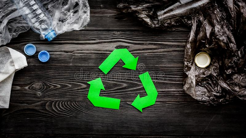 Green paper recycling sign among waste polyethylene bags and plastic bottles on grey wooden background top view.  stock image