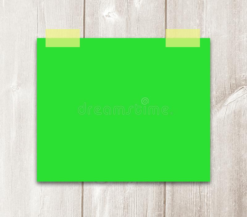 Green paper sheet on a wooden surface. stock photos