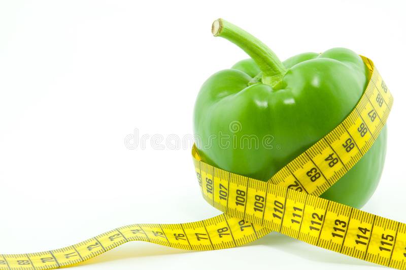 A green paprika. A green pepper with yellow tape measure stock photos