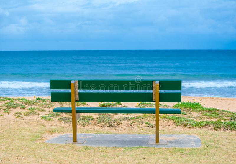 Green Park bench near the ocean, beach shows dark blue sea and horizon clouds sky day at Palm Beach, Northern Sydney, Australia. royalty free stock photos