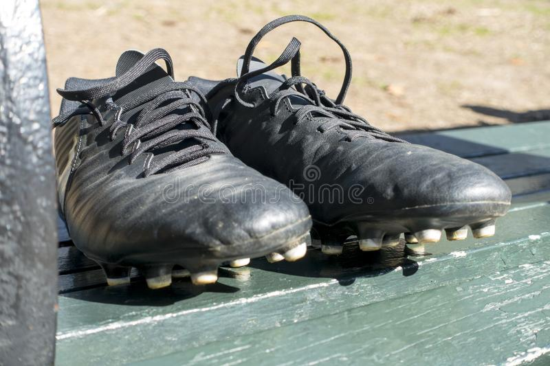 On a green park / diamond field bench a pair of used black cleat stock image