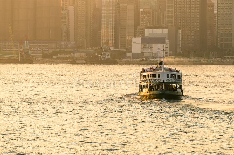 Green passenger Ferry in victoria harbour with cityscape background against morining sunrise, services between Kowloon and Hong stock image