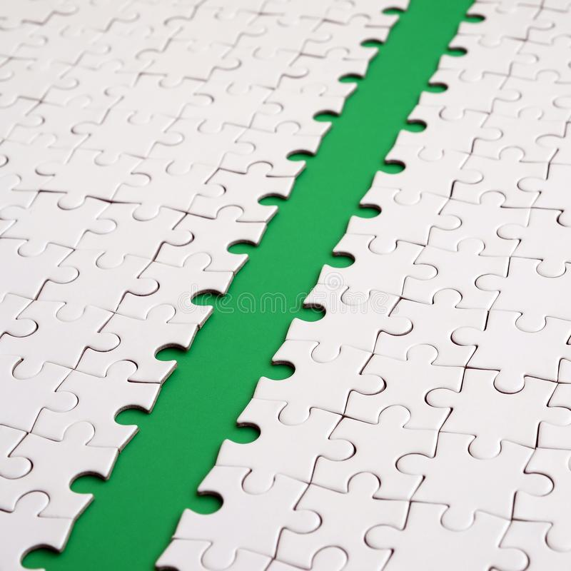 The green path is laid on the platform of a white folded jigsaw puzzle. Texture image with copy space for text.  stock photos