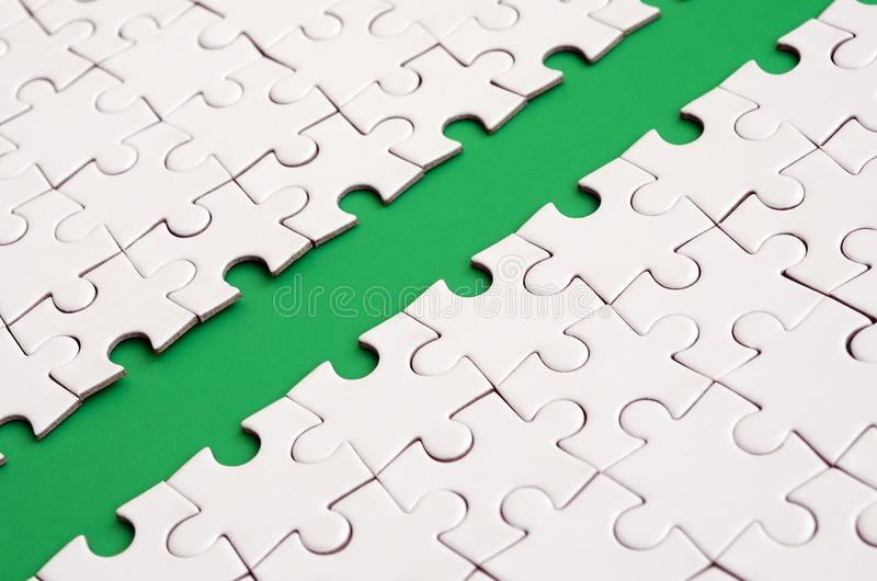 The green path is laid on the platform of a white folded jigsaw puzzle. Texture image with copy space for text.  stock images