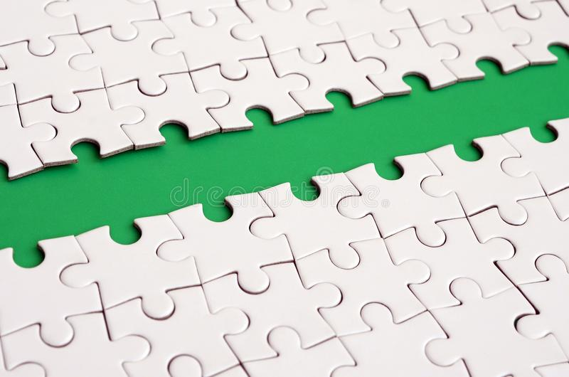 The green path is laid on the platform of a white folded jigsaw puzzle. Texture image with copy space for text.  stock photo