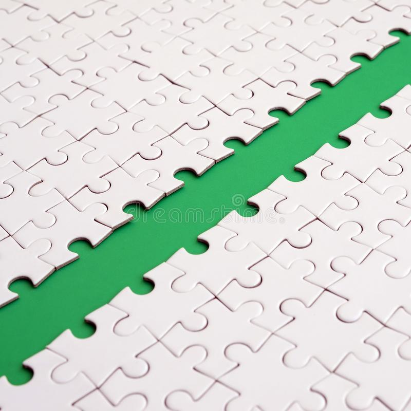 The green path is laid on the platform of a white folded jigsaw puzzle. Texture image with copy space for text.  royalty free stock photo