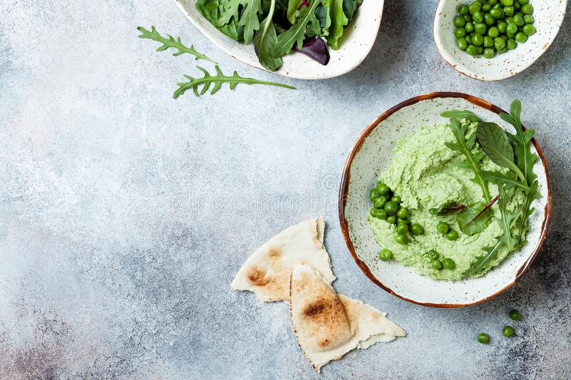 Green pea hummus spread or dip with mix salad leaves. Healthy raw summer appetizer, vegan, vegetarian snack. stock photos