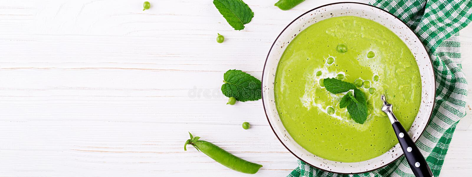 Green pea soup in bowl on wooden table. French cuisine. Banner. Top view royalty free stock photos