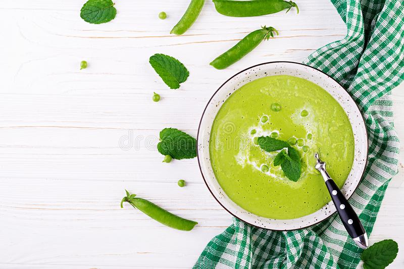 Green pea soup in bowl on wooden table. French cuisine. Top view stock image